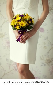 Bride's hands with wedding bouquet of violet and yellow flowers over stylish white dress. Vintage style. Close up. Indoor shot