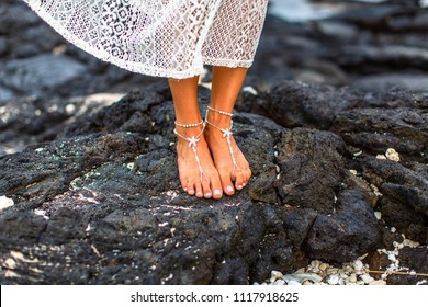 A bride's jewelry adorned feet on lava rock