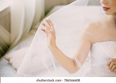 Bride's morning. Fine art wedding. Portrait of a young beautiful sexy tender bride with red lips in white lace wedding dress gracefully put hand on veil. Veil is thrown over her face. Closeup view