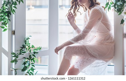bride`s morning, brides in peignoir by the window twined with greens
