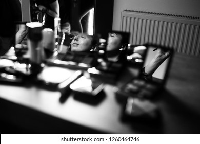Bride's morning. Reflection of bride's face in the mirrors of eye shadow palettes standing on the table