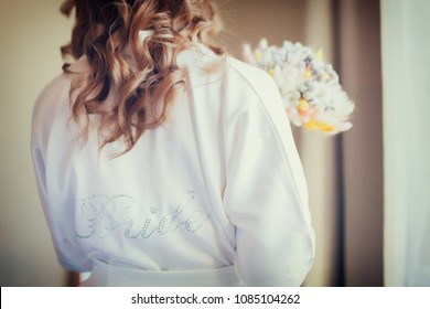 Bride's morning, woman wearing white silk dressing gown, holding wedding bouquet