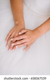 Bride's morning. young beautiful bride in white wedding dress gracefully put hand together. french nail concept.