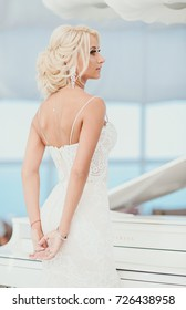 The bride's portrait, the distinguished gentle girl in a white dress at a grand piano