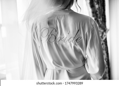 "Bride's robe with the inscription ""bride"". He stands with his back. near the window."