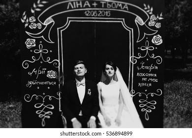 The brides sitting near decorative wall