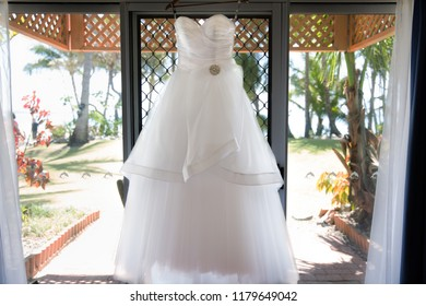 A Bride's wedding dress on hanger ready to be worn, framed by a window