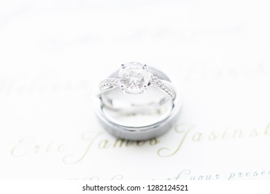 Bride's wedding ring with groom's ring on invitation