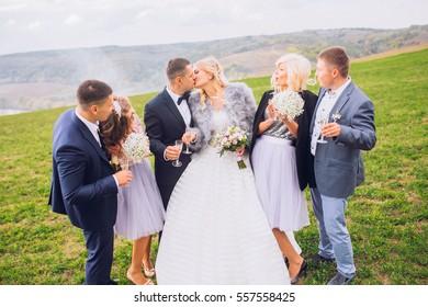 The brides,bridesmaids and groomsmen walking along field. having fun