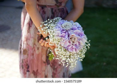 Bridesmade with beautiful dress holding bridal bouquet with flowers at wedding in park
