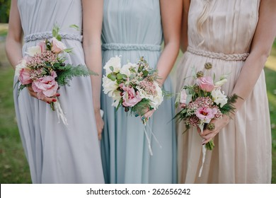 bridesmaid dresses in pastel are holding bouquets in a rustic style