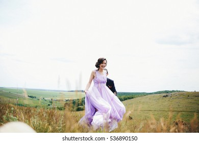The bridesmaid and groomsman running along field