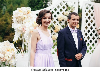 The bridesmaid with groomsman stand on the wedding ceremony