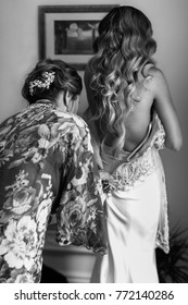 Bridesmaid helping the bride with the wedding dress.