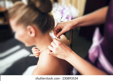 Bridesmaid helps to bride to put on jewelry. Shallow depth of field. Focused on necklace and finger of bridesmaid