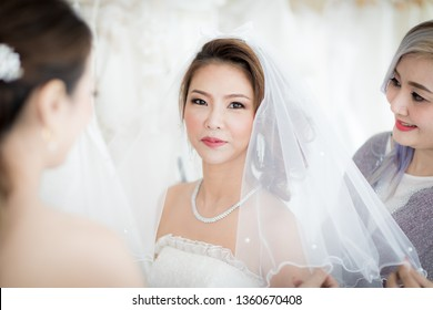 Bridesmaid helps bride to try wedding dress and makeup costume. with happy and funny. Concept for love and relationship of friends.