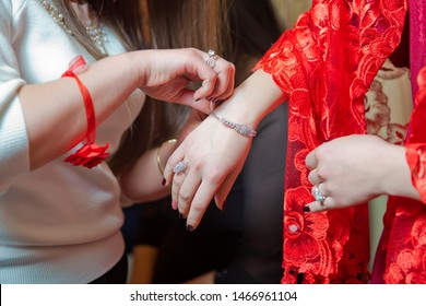 Bridesmaid helps to put a bracelet on his arm for the bride. bride putting on jewelry, focus on bracelet. Close up of groom giving his bride bracelet as symbol of his love on their henna day.