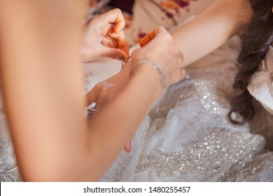 Bridesmaid helps to put a bracelet on his arm for the bride. bride putting on jewelry, focus on bracelet. Close up of groom giving his bride bracelet as symbol of his love on their wedding day
