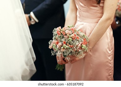 bridesmaid holding pink bouquet with roses in church at wedding ceremony, wedding spiritual couple, religious moment