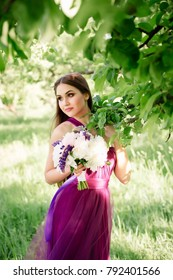 Bridesmaid with luxurious colorful fine art wedding bouquet of peonies and other flowers standing at ceremony near tree in purple violet dress smiling and looking at camera Prom graduation closeup.