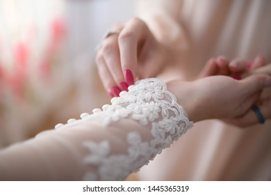 2dc80ef2a Bridesmaid or maid of honor helping the bride buttoning up the lacy  embroidered long sleeve of