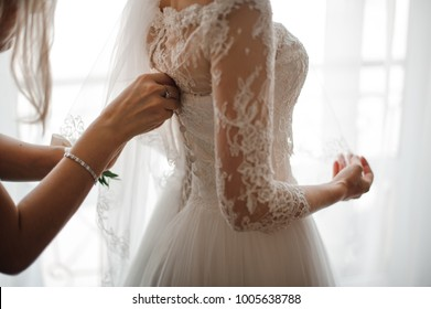 Bridesmaid making a bow-knot on the back of brides lacy white and beautiful wedding dress