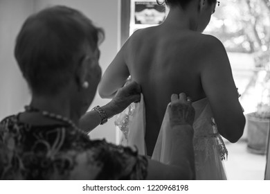 Bridesmaid preparing bride for the wedding day. Bridesmaid helps fasten a wedding dress the bride before the ceremony. Luxury bridal dress close up. Best wedding morning.