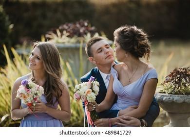 Bridesmaid in violet dress sits on the knees of groomsman