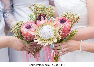 Bridesmaids and bride holding bouquets of Protea wedding flowers together with pink ribbons and gyp closeup