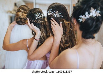 The bridesmaids and the bride straighten their hairstyles and hold on to their hair. Morning of the bride with best friends. Wedding bachelorette party. Photography, concept.