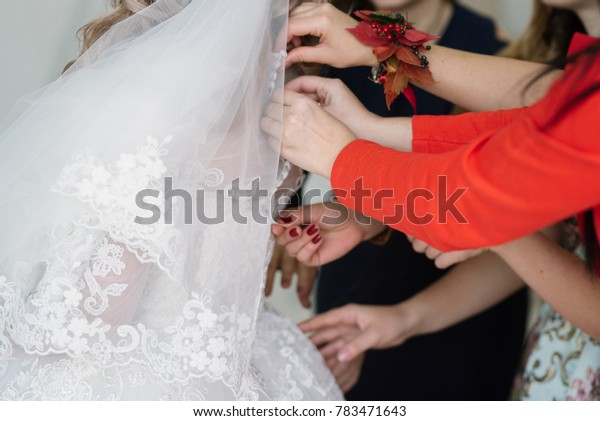 The bridesmaids are buttoning up the dress
