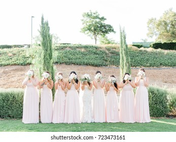 Bridesmaids Covering Faces with Flowers