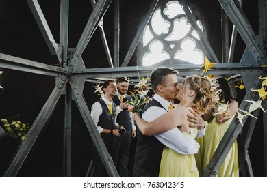 Bridesmaids and groomsmen laugh standing in the room with yellow and white paper birds
