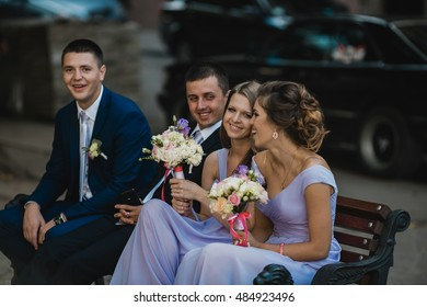 Bridesmaids and groomsmen sit on the bench outside