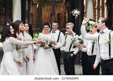 Bridesmaids and groomsmen throw their bouquets over newlyweds posing outside