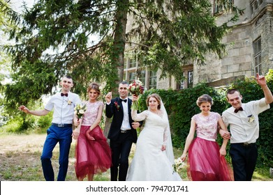 Bridesmaids with groomsmen and wedding couple jumping, dancing and having fun next to an old building.