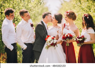 Bridesmaids have fun while wlking with bride in the park