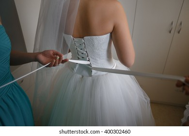 Bridesmaids are helping to bride with dress