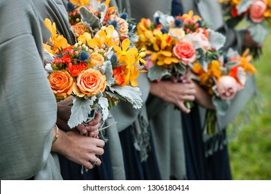 bridesmaids holding their wedding bouquets of flowers with yellow, red, blue and orange flowers