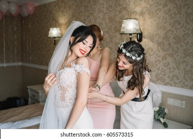bridesmaids lace up the corset of gentle bride in the morning