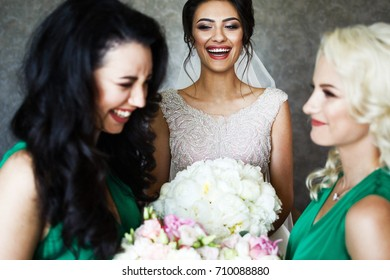 Bridesmaids look in each other eyes standing before smiling bride