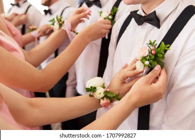 Bridesmaids put small bouquets on shirt of groomsmen at wedding day