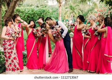 Bridesmaids stand around gorgeous Indian wedding couple