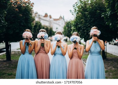 Bridesmaids at wedding with bouquets in hands. Girl in colored dresses for wedding.