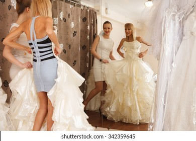 A Bride-To-Be Trying On A Wedding Dress with a girlfriend and having fun  in a Bridal Boutique