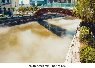 Bridge across Gombak river. Misty water. Kuala Lumpur cityscape. Connection concept. Travel to Malaysia. River embankment. City tour. Tourism industry. Urban background. City centre park.