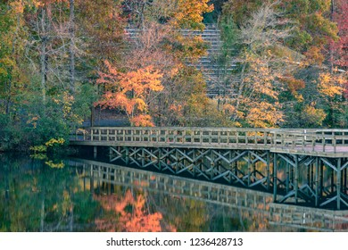 Bridge and autumn leaves reflecting off of the water