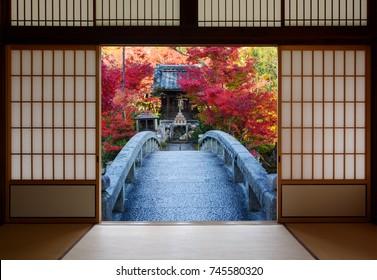 Bridge and autumn trees seen through the open doors of an old Japanese dojo