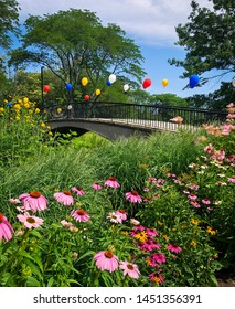 Bridge with balloons that are different colors and flowers in foreground.
