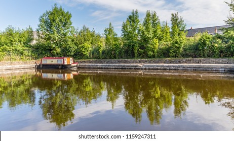 Bridge and barge reflecting in the water of Brecon Canal basin  in Brecon, Beacons National Park, Wales, UK
